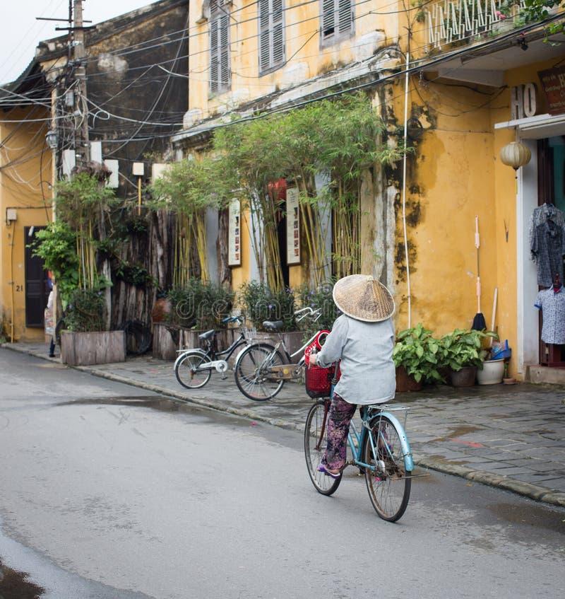 Una mujer biking en la calle en Quang Nam, Vietnam imagen de archivo