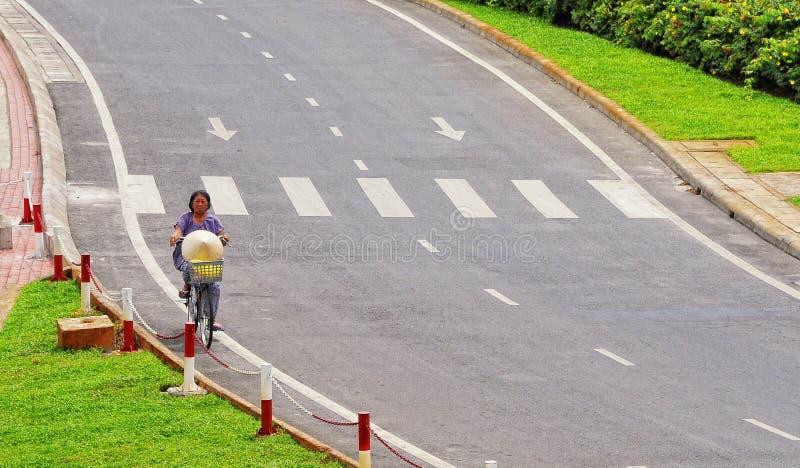 Una mujer biking en la calle en Saigon, Vietnam fotografía de archivo libre de regalías