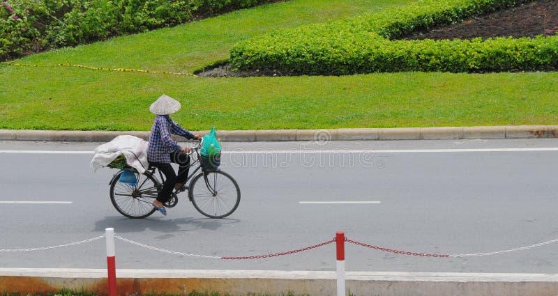 Una mujer biking en la calle en Saigon, Vietnam foto de archivo libre de regalías