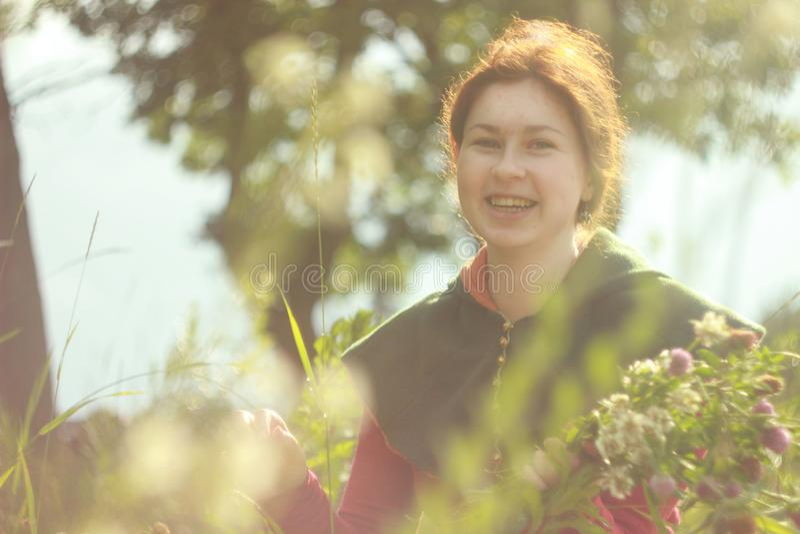 Una mujer blanca caucásica joven feliz con el pelo rojo largo es sonriente y de risa con un ramo de flores en sus manos en un cam fotos de archivo