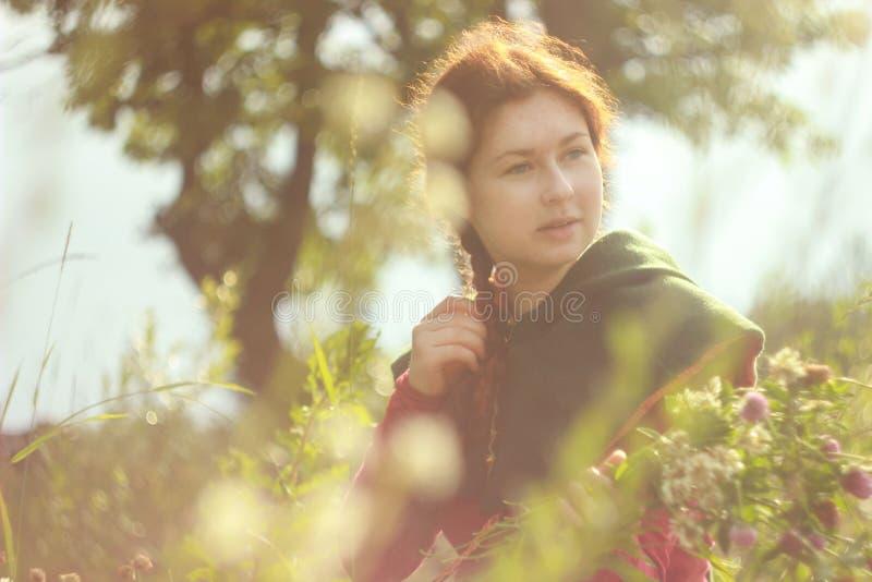 Una mujer blanca caucásica joven feliz con el pelo rojo largo es sonriente y de risa con un ramo de flores en sus manos en un cam imagen de archivo