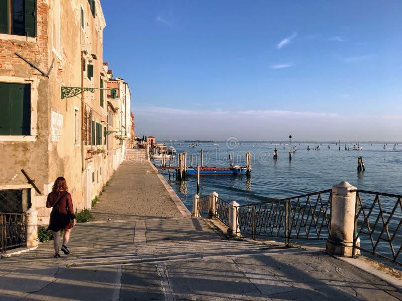 Una mujer bonita joven que camina a lo largo de la costa sola en el extremo norte de Venecia Italia en la madrugada con la Veneci fotografía de archivo
