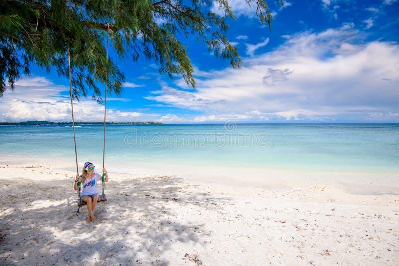 Una mujer bonita que se sienta en un oscilación en una playa blanca hermosa de la arena foto de archivo libre de regalías