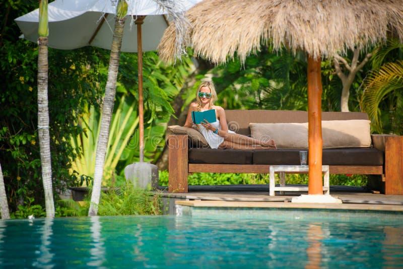 Una mujer bonita que sienta en la sombra tropical una piscina foto de archivo