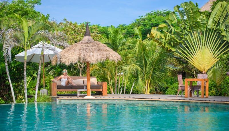 Una mujer bonita que sienta en la sombra tropical una piscina 2 fotografía de archivo libre de regalías
