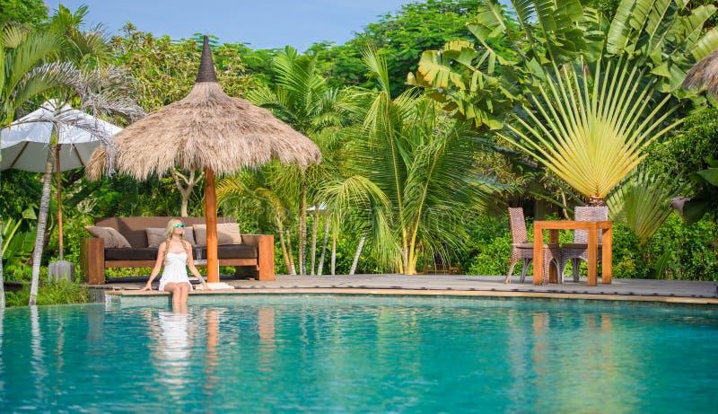 Una mujer bonita que sienta en la sombra tropical una piscina 3 fotos de archivo libres de regalías