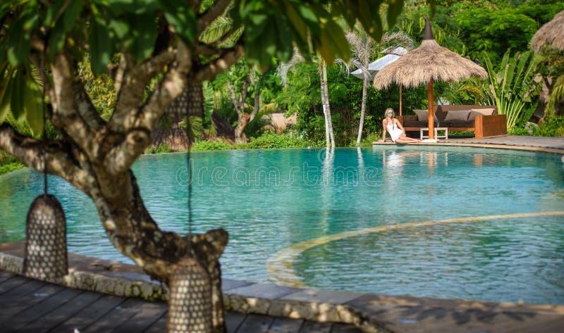 Una mujer bonita que sienta en la sombra tropical una piscina 4 fotografía de archivo
