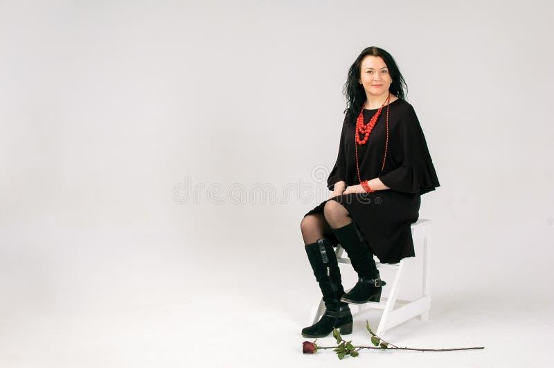 Una mujer cabelluda oscura hermosa de 40 años en un vestido negro y gotas étnicas rojas se sienta en una silla Retrato en integra foto de archivo libre de regalías