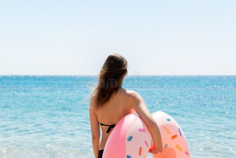 Una mujer camina en la agua de mar Muchacha que se relaja en el anillo inflable en la playa Vacaciones de verano y concepto de la foto de archivo