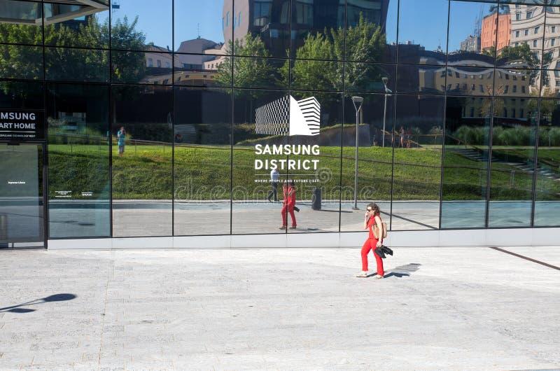 Una mujer camina fuera del edificio electrónico de Samsung Italia en la nueva zona de Porta Nuova en Milán, Italia foto de archivo