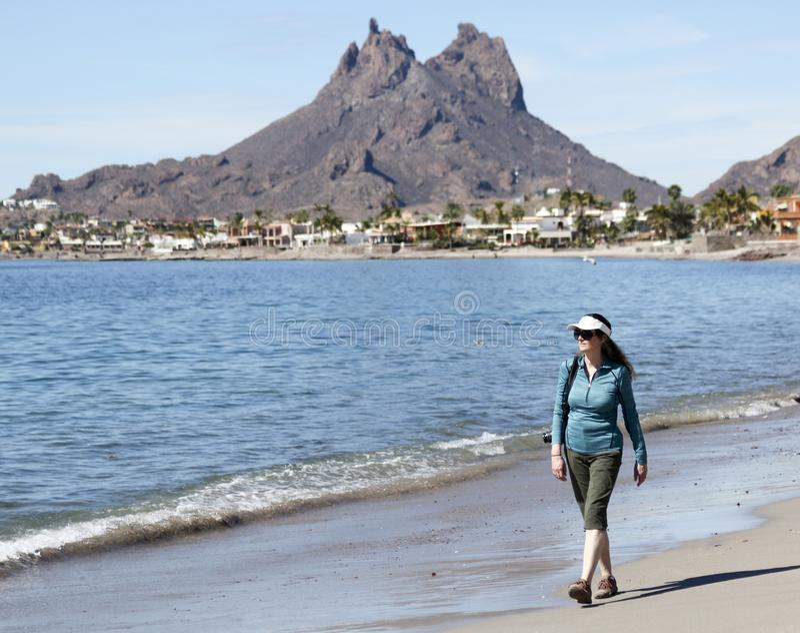 Una mujer camina la playa, montaña de Tetakawi detrás, San Carlos, M imagen de archivo libre de regalías