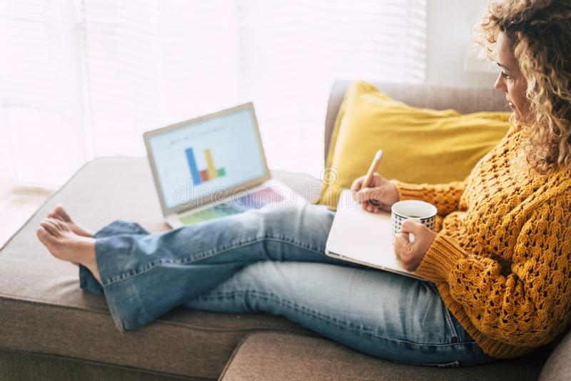 Una mujer caucásica adulta relajada en el trabajo en casa con ordenador portátil personal - economía y alternativa comercial