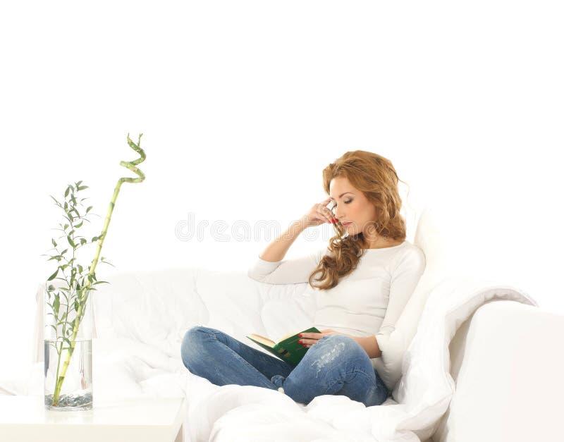 Una mujer caucásica joven que lee un libro en un sofá foto de archivo