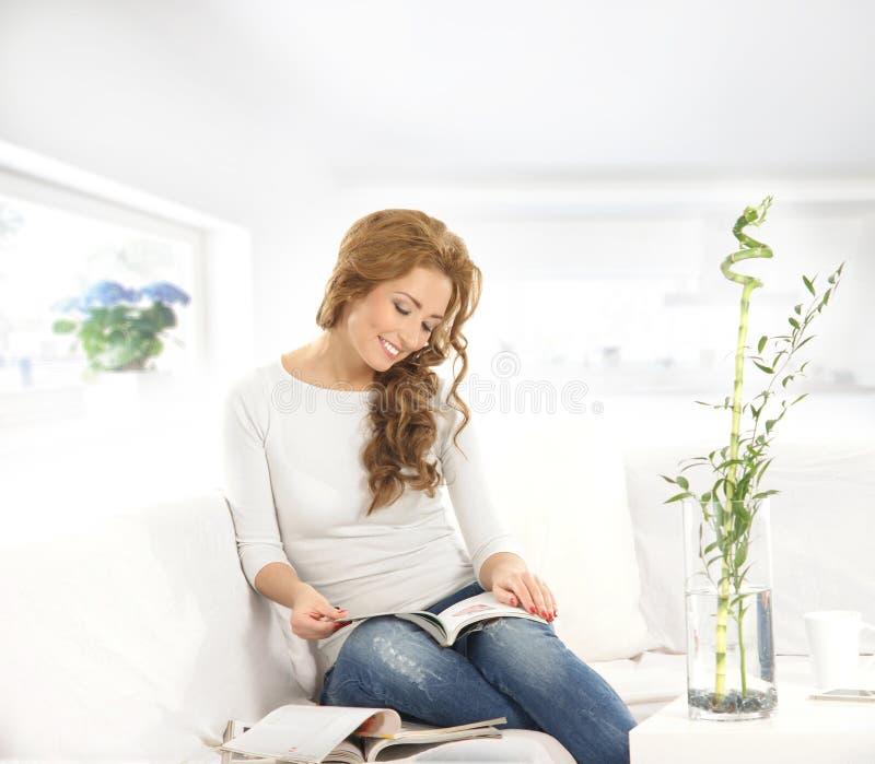 Una mujer caucásica joven que lee un libro en un sofá imagen de archivo
