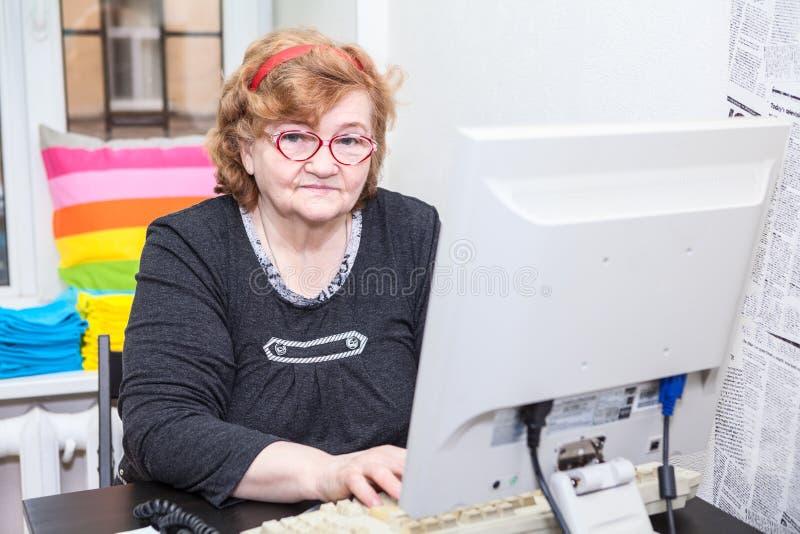 Una mujer caucásica mayor que trabaja con el ordenador imagen de archivo libre de regalías