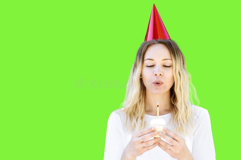 Una mujer celebra su cumpleaños con una magdalena y una vela con un sombrero del partido en la pantalla verde imagen de archivo
