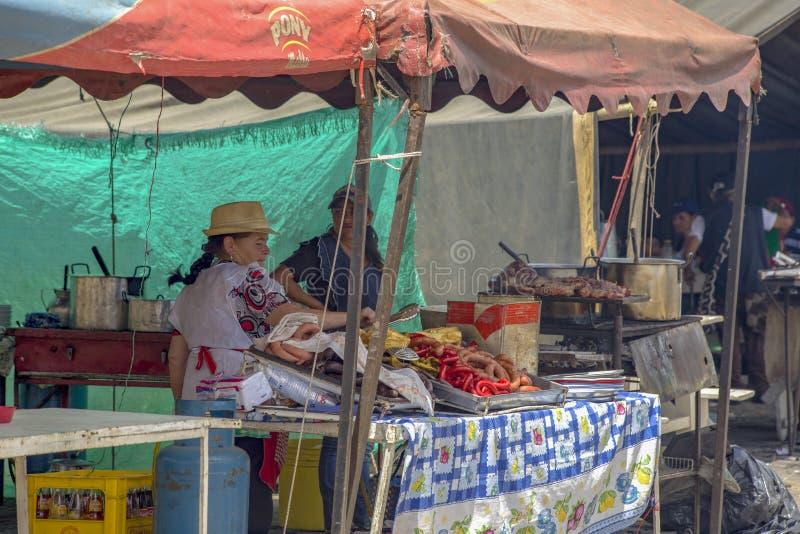 Una mujer cocina la comida típica foto de archivo libre de regalías