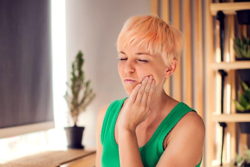 Una mujer con dolor en sus dientes se está sosteniendo la cara interior Gente, salud y concepto médico fotos de archivo