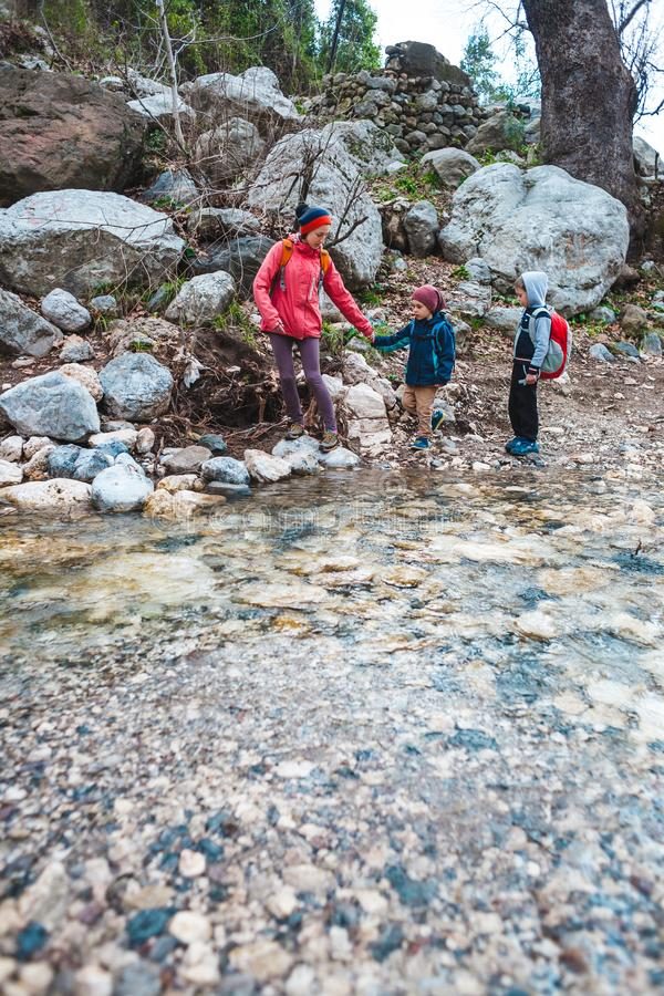 Una mujer con dos niños camina a lo largo de un río de la montaña fotos de archivo