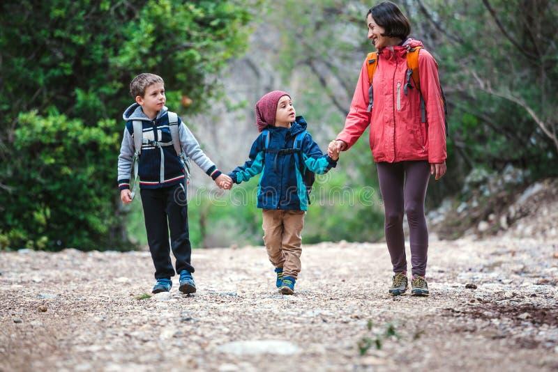 Una mujer con dos niños pasa a través del bosque fotos de archivo