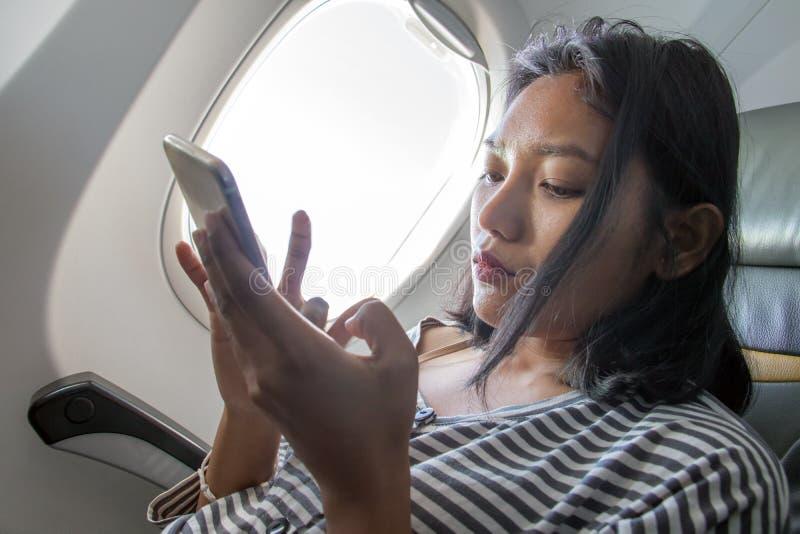 Una mujer con el móvil en un avión que vuela foto de archivo