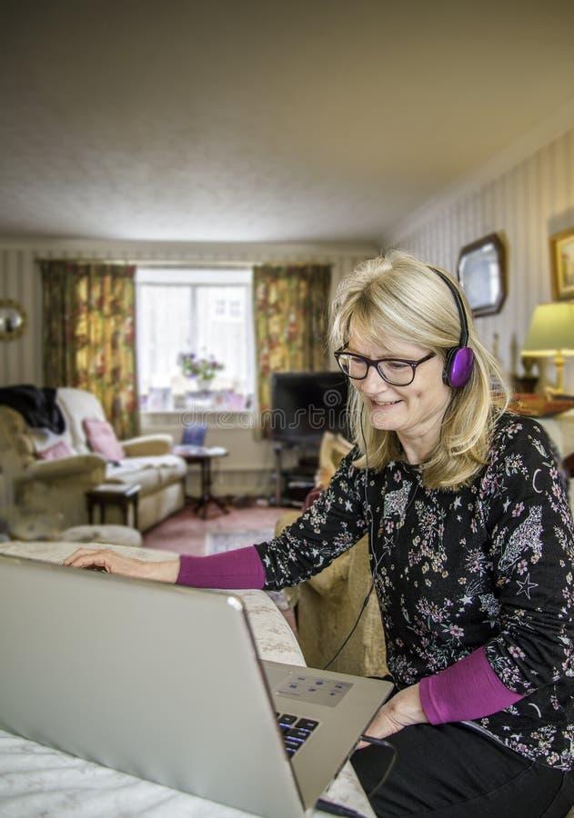 Una mujer con el ordenador portátil que sonríe, divertida en el contenido en la pantalla imagen de archivo