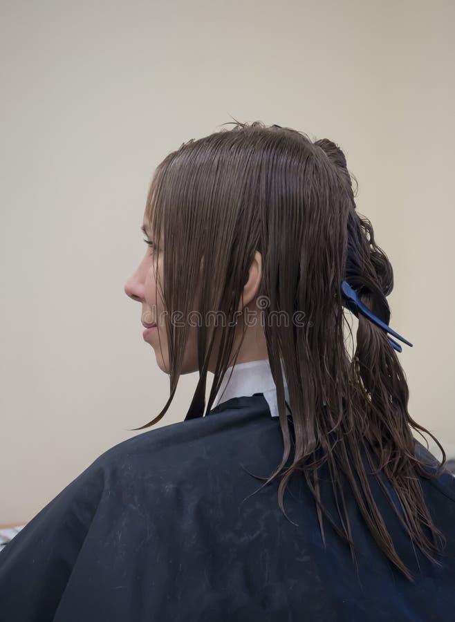 Una mujer con el pelo mojado antes de un corte de pelo en un salón de belleza foto de archivo