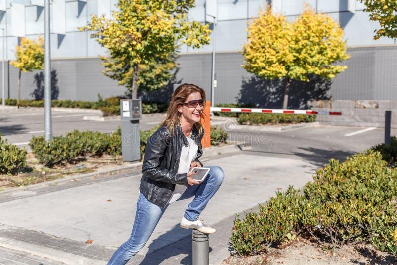 Una mujer con las pausas de los vidrios negros y de la ropa casual a estirar, en el medio de un día soleado foto de archivo libre de regalías