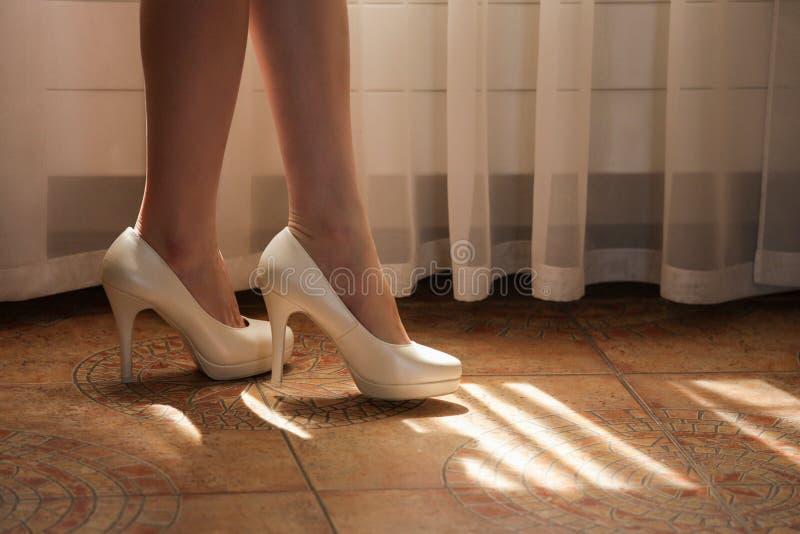 Una mujer con las piernas desnudas en los zapatos blancos en los tacones altos imagen de archivo libre de regalías