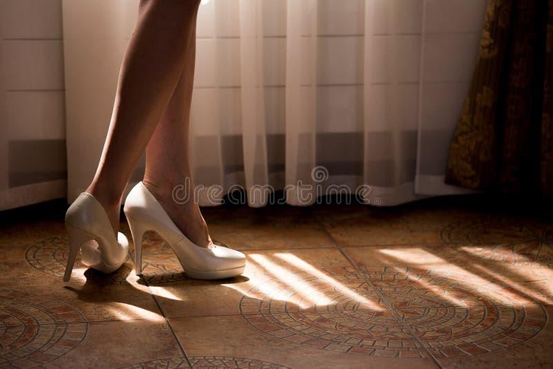 Una mujer con las piernas desnudas en los zapatos blancos en los tacones altos foto de archivo libre de regalías