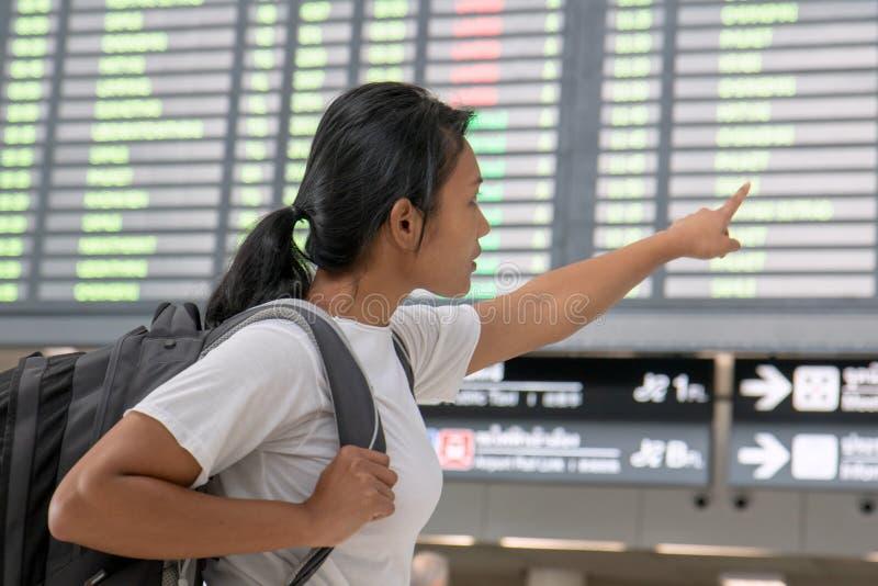 Una mujer con una mochila que muestra conexiones de un vuelo foto de archivo libre de regalías