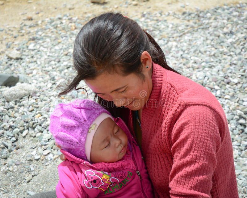 Una mujer con su niño en el pueblo tibetano en Ladakh, la India imagen de archivo