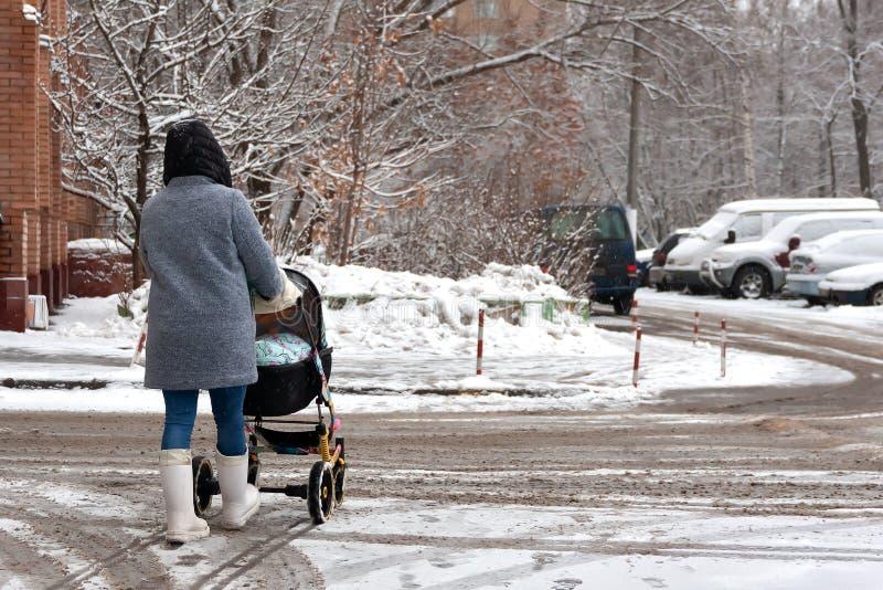 Una mujer con un cochecito y un niño entra nevadas fuertes Paseo con el bebé en el cochecito de niño Limpió gravemente las calles imagen de archivo