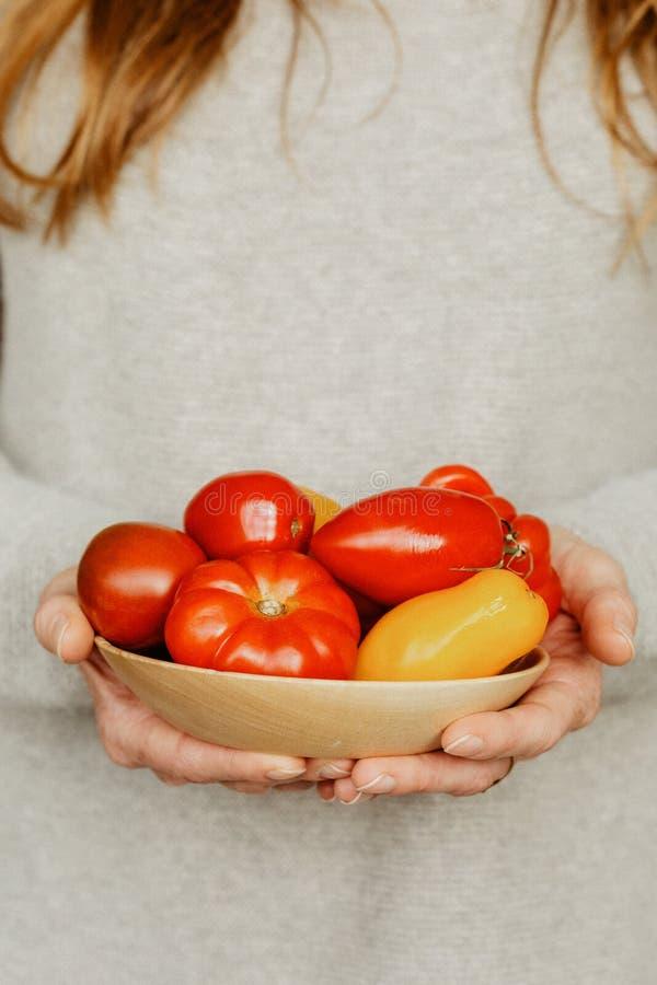 Una mujer con un cuenco de tomates y de pimientas imagen de archivo