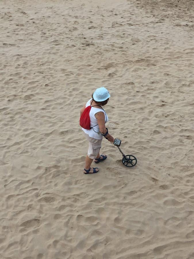 Una mujer con un detector de metales en la playa de Gijón Asturias España imagen de archivo libre de regalías