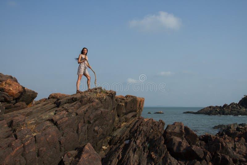 Una mujer con un personal encima de una roca El conquistador del top de la montaña foto de archivo libre de regalías