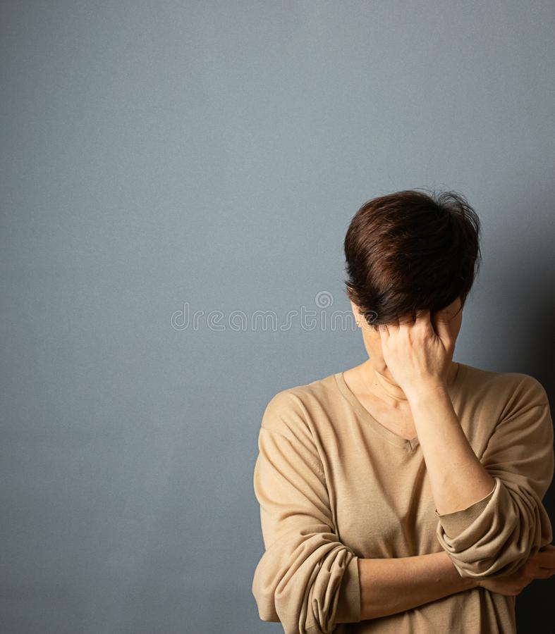 Una mujer cubre su cara con su mano, soportes contra la pared Retrato de la mujer en un fondo gris foto de archivo libre de regalías