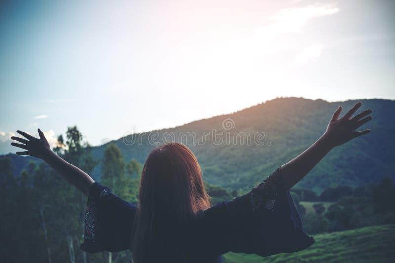 Una mujer da vuelta a retroceder y a estirar los brazos con la naturaleza y la montaña imágenes de archivo libres de regalías