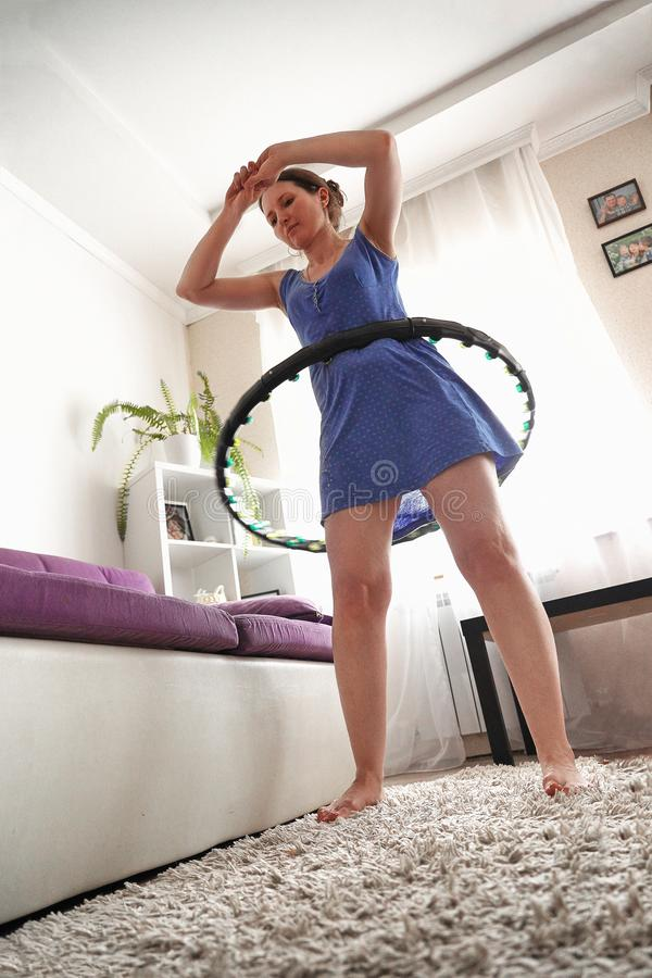 Una mujer da vuelta a un aro del hula en casa uno mismo-entrenamiento con un aro fotografía de archivo libre de regalías