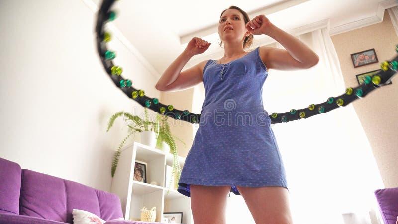 Una mujer da vuelta a un aro del hula en casa uno mismo-entrenamiento con un aro fotografía de archivo