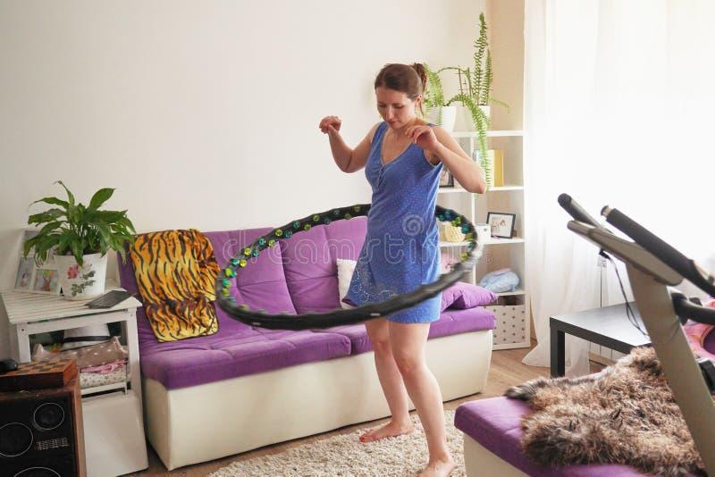 Una mujer da vuelta a un aro del hula en casa uno mismo-entrenamiento con un aro imágenes de archivo libres de regalías