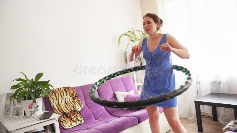 Una mujer da vuelta a un aro del hula en casa uno mismo-entrenamiento con un aro imagenes de archivo