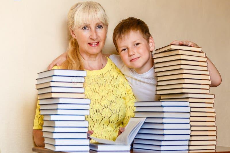Una mujer de la edad del retiro y un colegial del muchacho en la tabla con una pila grande de libros imagen de archivo libre de regalías