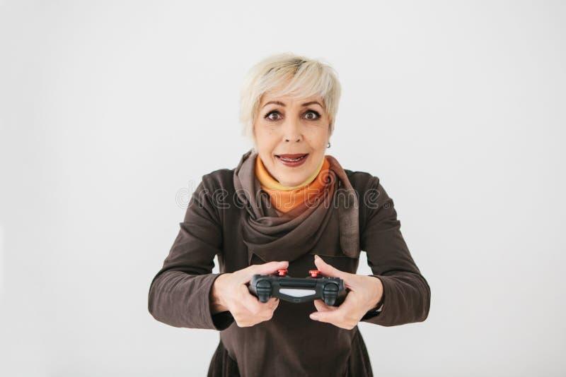 Una mujer de los ancianos juega un videojuego y los gestos que ella ganó Persona mayor y tecnología moderna foto de archivo libre de regalías