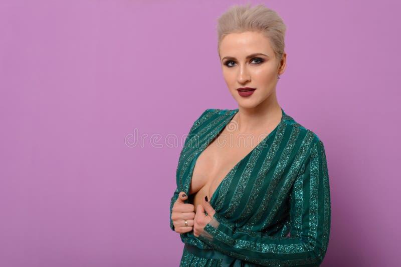 Una mujer de mediana edad atractiva con un pecho hermoso se aferra al escote de un vestido verde cerca del fondo violeta fotos de archivo libres de regalías