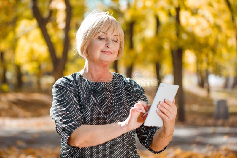 Una mujer de mediana edad atractiva que camina en un parque del otoño con los artilugios en un fondo borroso imagen de archivo libre de regalías