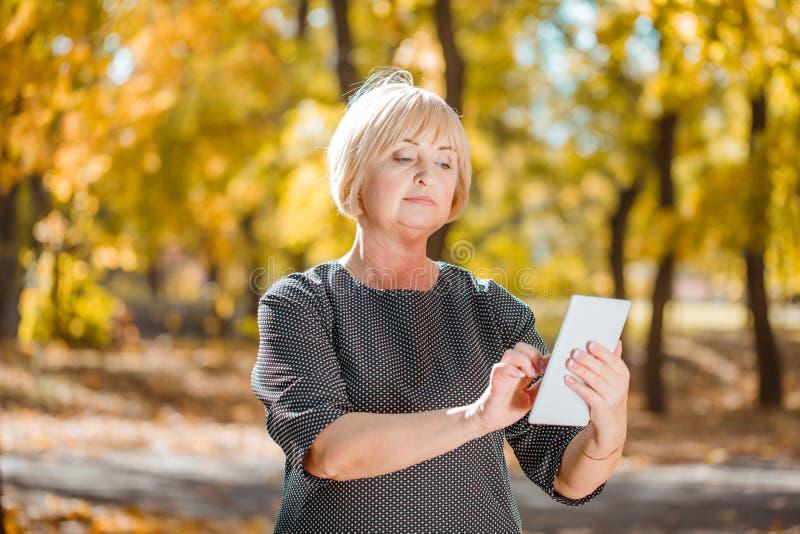 Una mujer de mediana edad atractiva que camina en un parque del otoño con los artilugios en un fondo borroso imágenes de archivo libres de regalías
