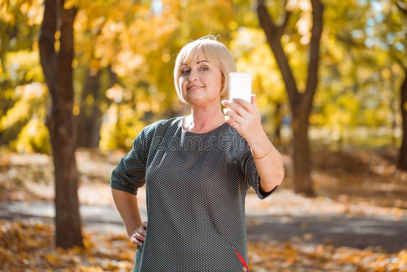 Una mujer de mediana edad atractiva que camina en un parque del otoño con los artilugios en un fondo borroso imagen de archivo