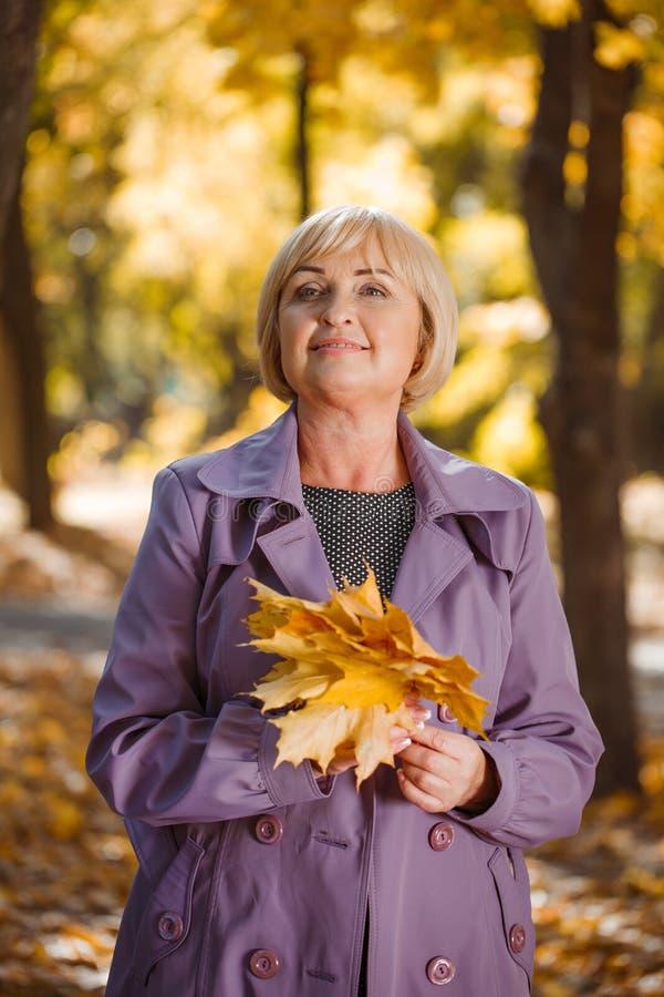 Una mujer de mediana edad atractiva que camina en un parque del otoño en un fondo borroso fotos de archivo