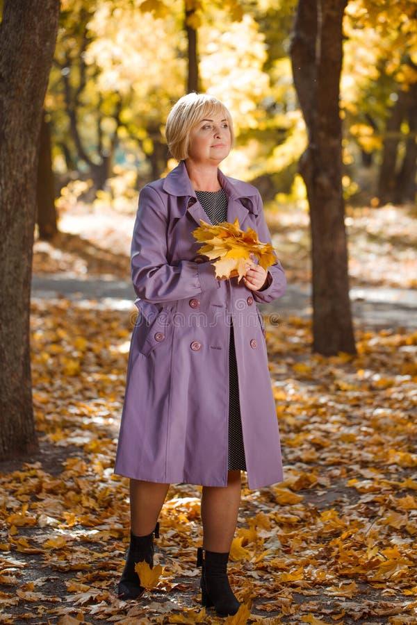 Una mujer de mediana edad atractiva que camina en un parque del otoño en un fondo borroso foto de archivo libre de regalías